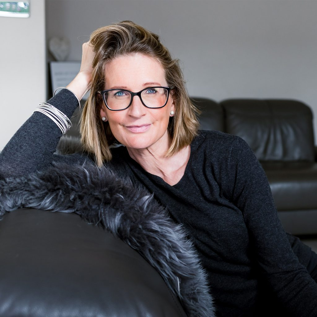 Leigh Howes on black sofa looking straight at camera